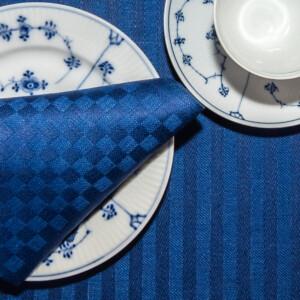 Blå ordern linne servetter tabletter på tallrik med bestick Klässbols Linneväveri Hanne Vedel bordsdukning tillsammans med kaffe och vitt och blått porslin