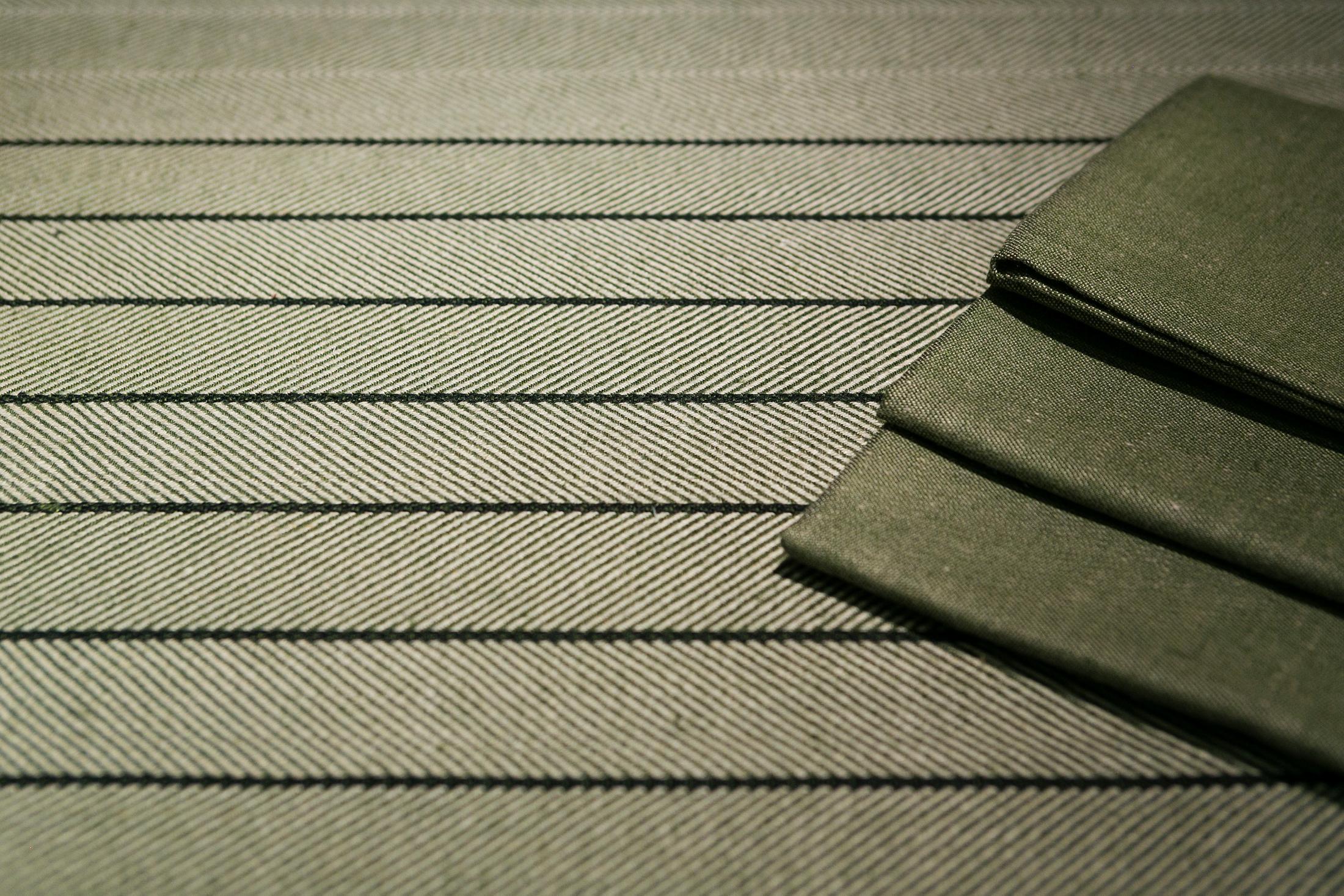 Mossgrön Gärdet med svart rand linneduk. Satin servett i mossgrönt av Klässbols Linneväveri. Design av Karl-Åke Johansson